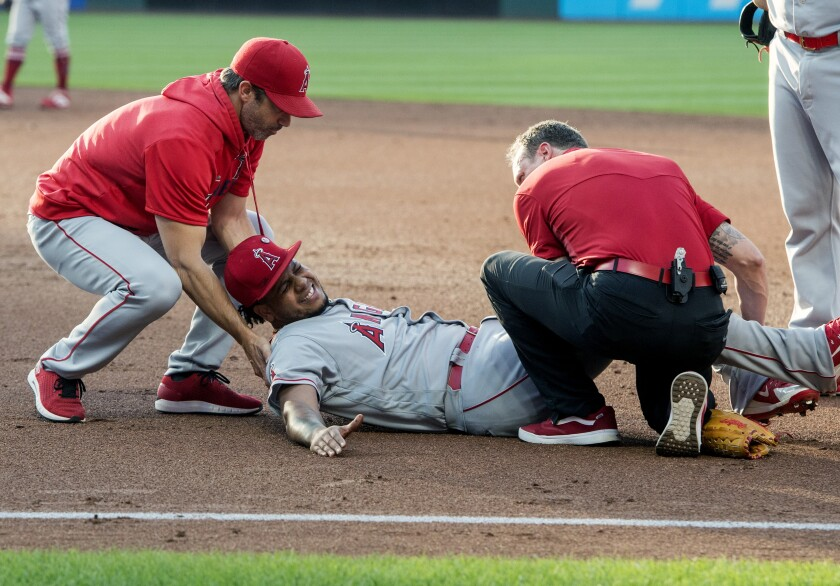 Angels pitcher Felix Pena lays on the ground grimacing.