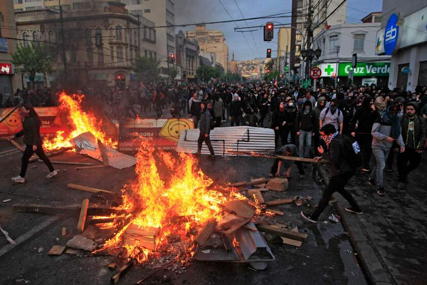 Protesters light bonfires in Vaparaiso, Chile. Chilean President Sebastian Pinera announced Saturday the suspension of the increase in the price of metro tickets, which had triggered violent protests.