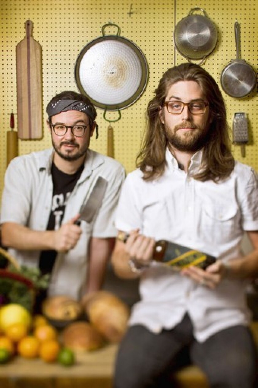 Evan George, left, and Alex Brown in Evan's kitchen. Their food blog is called Hot Knives.