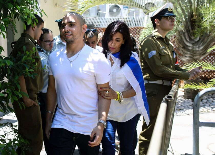 Israeli soldier Elor Azaria, who shot dead a wounded Palestinian assailant in March 2016, is escorted by his mother Oshra while she is draped in an Israeli flag, to attend a hearing at a military court in Tel Aviv on July 30, 2017.