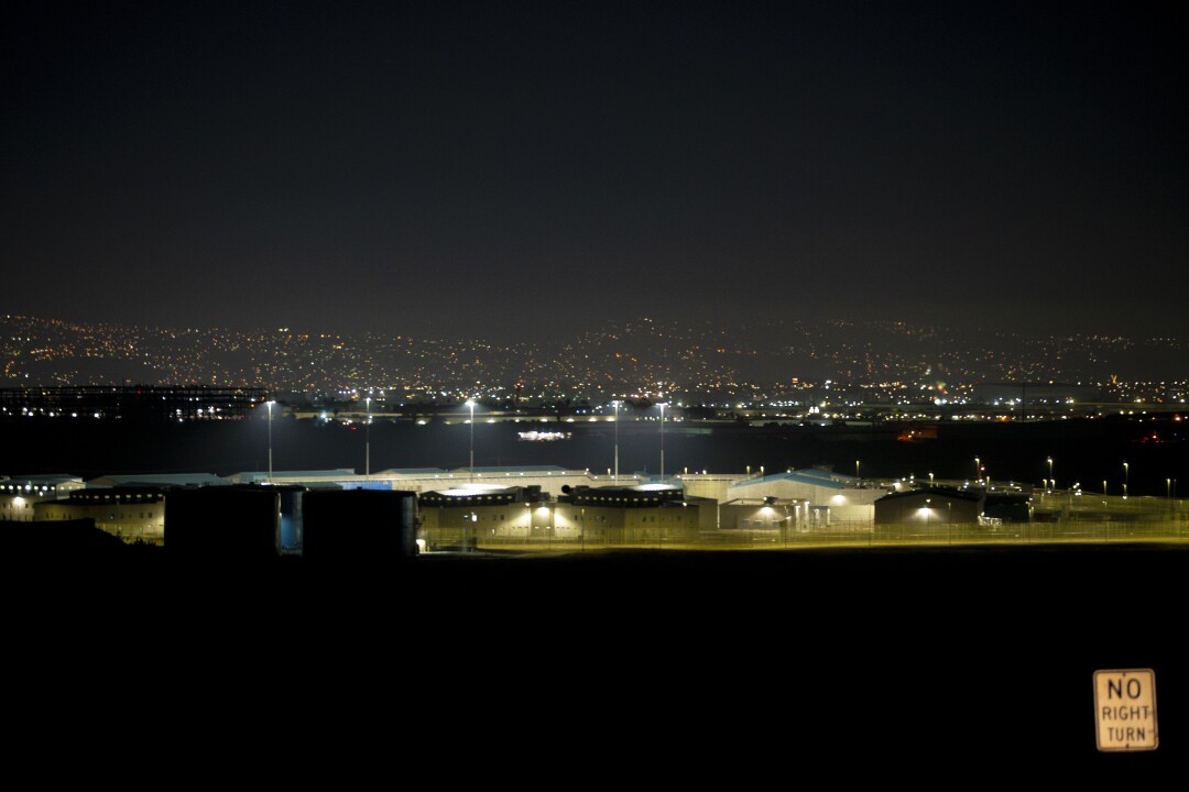 Otay Mesa Detention Center at night with the lights of Tijuana visible in the distance behind the building
