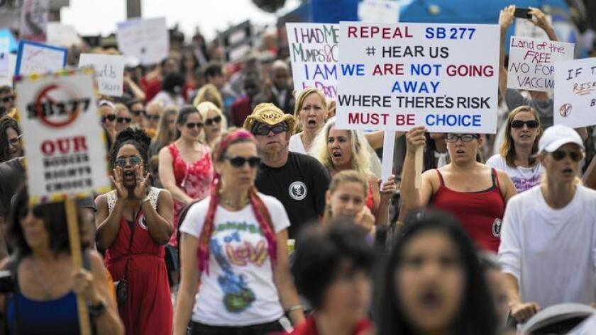 Varios cientos de opositores de la nueva ley de vacunación de California marchan el viernes desde el muelle de Santa Mónica hasta el ayuntamiento de la ciudad.
