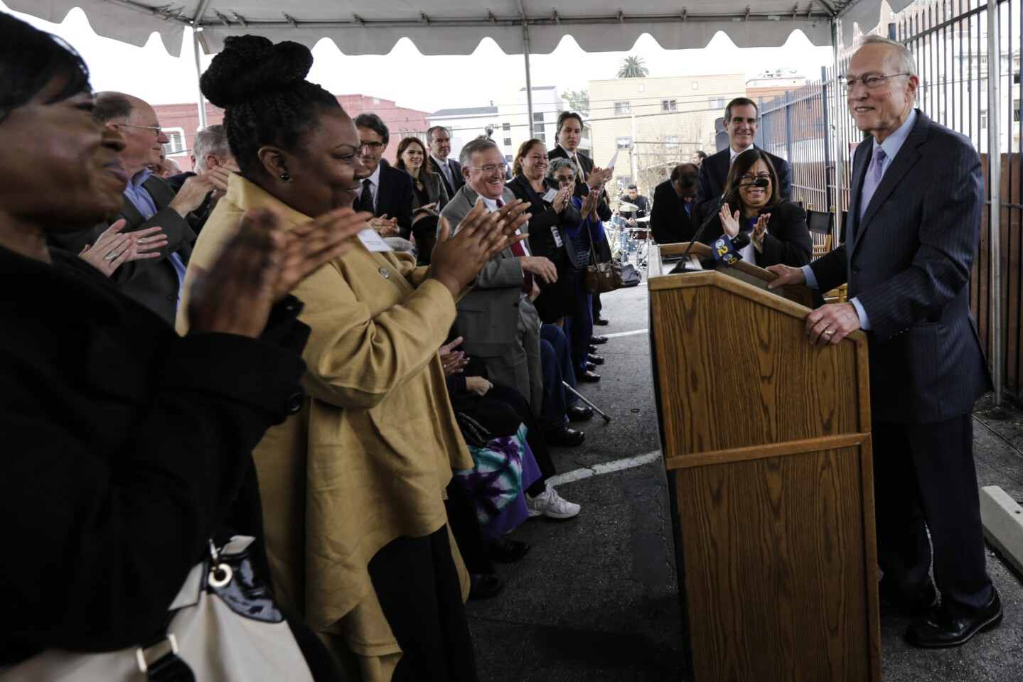 Ron Olson, right, gets a standing ovation at the groundbreaking ceremony of the Ron Olson Justice Center, named after him, at the corner of 8th Street and Union Avenue in Los Angeles.