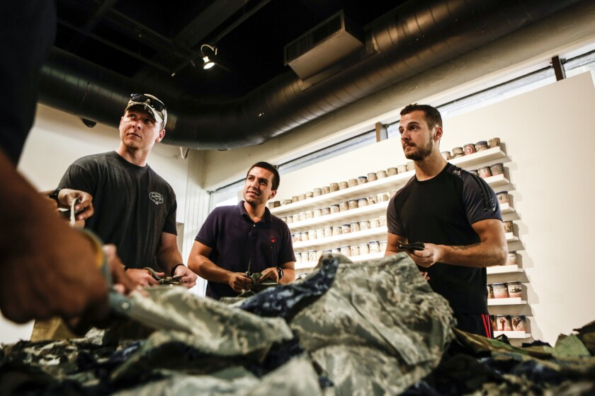 """Artist Drew Cameron (off-camera to the left) leads a workshop """"Combat Paper"""" based on his work with veterans."""
