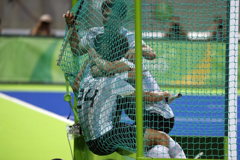 Players from Argentina celebrate inside the net cage after beating Belgium during a men's field hockey gold medal match at the 2016 Summer Olympics in Rio de Janeiro, Brazil, Thursday, Aug. 18, 2016. (AP Photo/Dario Lopez-Mills)