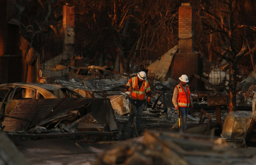 Pacific Gas & Electric Co. workers make their way through the fire-ravaged neighborhood of Coffey Park in Santa Rosa on Saturday.