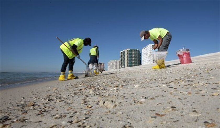 Oil spill workers continue the process of cleaning tar balls and oil from the beaches of Orange Beach, Ala., Tuesday, Nov. 9, 2010. A BP official said deep cleaning operations would continue along the coast for some time. (AP Photo/Dave Martin)