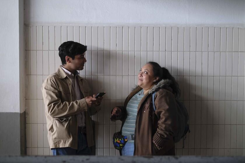 Un hombre y una mujer apoyados contra una pared y hablando.