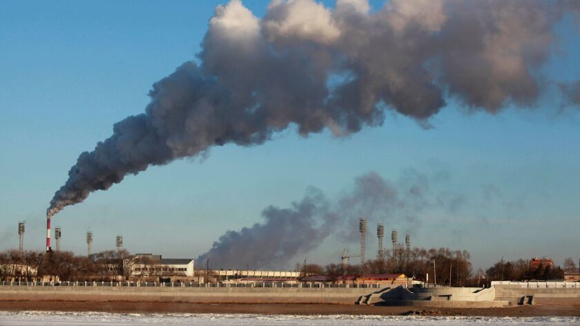 A heating factory spews smoke in northeastern China's Heilongjiang province. Carbon emissions from burning fossil fuels have decreased, but scientists say it's not enough to stave off dangerous global warming.