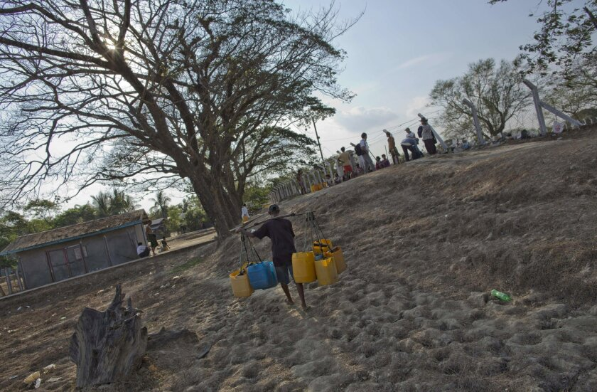 In this May 12, 2016 photo, a man walks on dry and cracked earth with empty plastic containers to collect drinking water from a fenced-off pond in Dala township, south of Yangon, Myanmar. Myanmar's dry season, which typically runs from April through May, has been compounded this year by an El Nino-induced drought that added several months to the water shortage affecting Dala township. (AP Photo/Gemunu Amarasinghe)