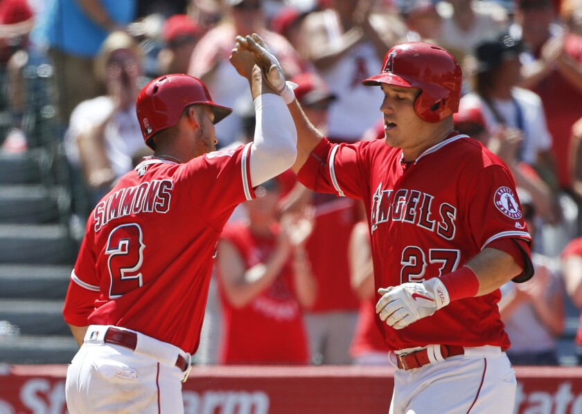 Angels outfielder Mike Trout (27) celebrates with shortstop Andrelton Simmons after hitting a two-run home run in the seventh inning.