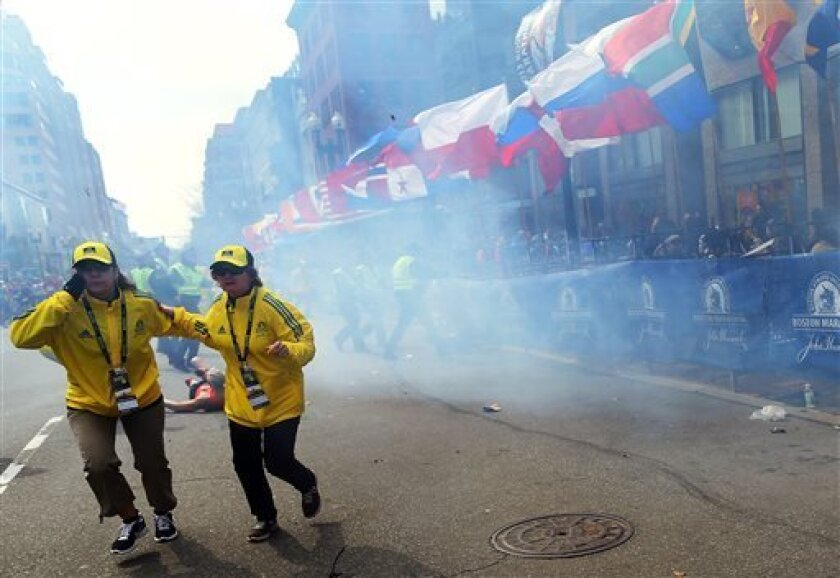 People react to an explosion at the 2013 Boston Marathon in Boston, Monday, April 15, 2013. Two explosions shattered the euphoria of the Boston Marathon finish line on Monday, sending authorities out on the course to carry off the injured while the stragglers were rerouted away from the smoking sit