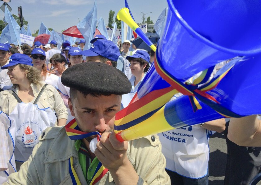 Aurel Selaru, a Romanian teachers union leader, blows a horn during a march in Bucharest, Romania, Wednesday, June 1, 2016. Thousands of Romanian teachers have demonstrated in Bucharest outside the government's main offices before marching through the capital to demand higher salaries. (AP Photo/Ni