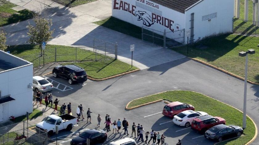 Students are evacuated in February from Marjory Stoneman Douglas High School in Parkland, Fla., after a shooter opened fire; 17 people died.