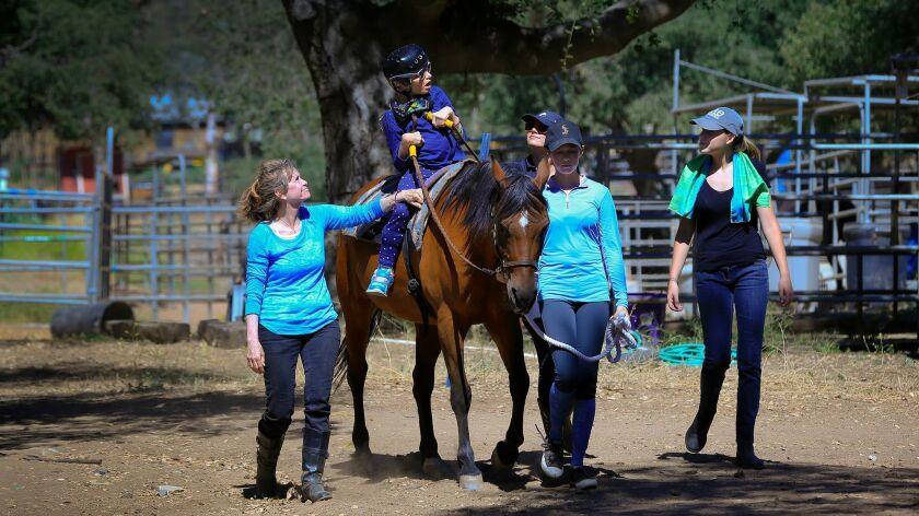 Surrounded by volunteers, Kimberly Penick goes on a horseback ride that takes her around the horse arena and stables in east Poway at the Ride Above Disability Therapeutic Riding Center. Left-right, Sharon Mann, Kimberly Penick, Danica Taylor, Natalie Parker and Riley Burkart.