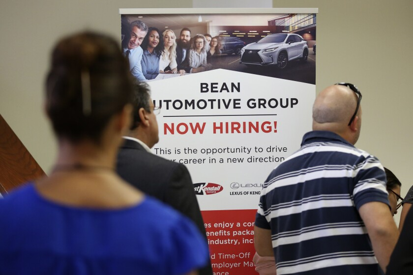 FILE - In this Sept. 18, 2019, file photo people stand in line to inquire about jobs available at the Bean Automotive Group during a job fair designed for people fifty years or older in Miami. On Tuesday, Feb. 11, 2020, the Labor Department reports on job openings and labor turnover for December. (AP Photo/Lynne Sladky, File)
