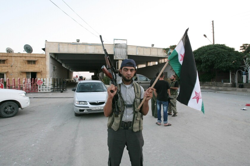 A rebel fighter is seen holding a rifle and a Syrian flag at the Bab al-Salameh border crossing into Turkey in July 2012. According to one opposition group, more than 40 people were killed in a bomb blast at the crossing Thursday.