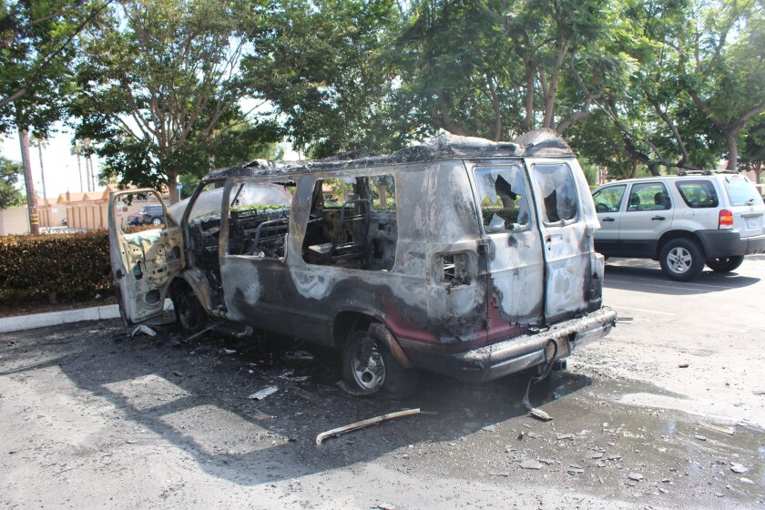 A burned out van in a parking lot surrounded by trees.