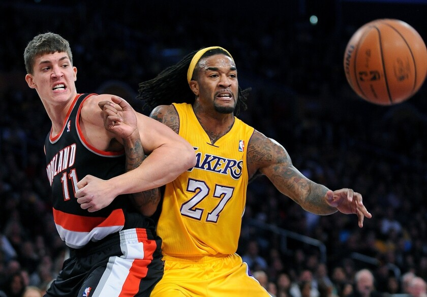 The Lakers' Jordan Hill locks up with Portland's Meyers Leonard in a game at Staples Center on Dec. 28.