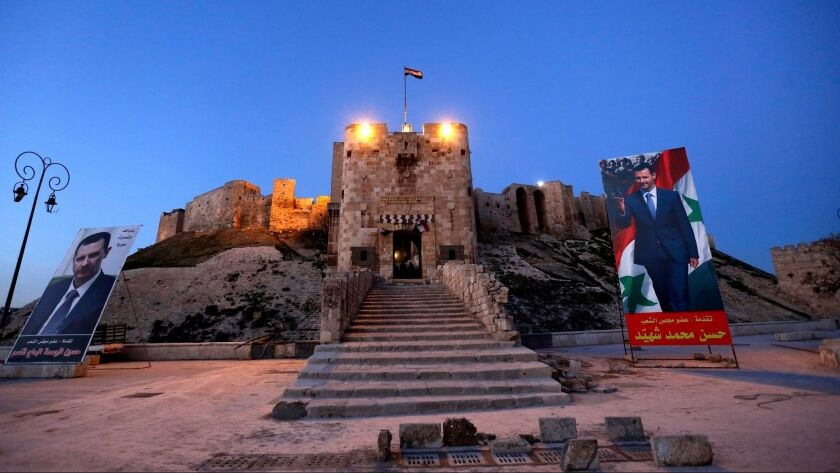 A view of the Aleppo Citadel in the old city Jan. 31, showing portraits of Syrian President Bashar Assad. The Citadel is among the historic sites that has not been badly damaged in the civil war.
