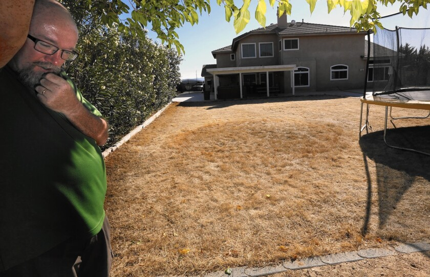 """Lance Arnt, an Apple Valley high school teacher, said he was able to get his water bill down to about $85 a month only after severely cutting back his water use. """"""""Our backyard is a field of hay, basically,"""" he said."""