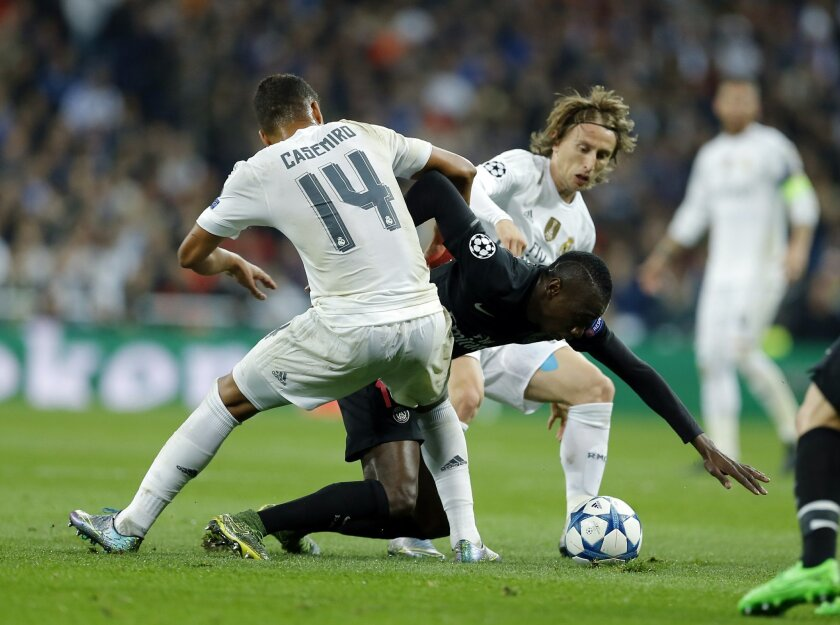 PSG's Blaise Matuidi, center, is stopped by Real Madrid's Luka Modric, right, and Henrique Casemiro during the Champions League group A soccer match between Real Madrid and PSG at the Santiago Bernabeu stadium in Madrid, Tuesday, Nov. 3, 2015. (AP Photo/Francisco Seco)