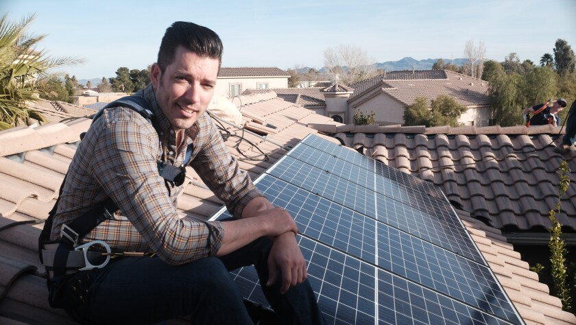 Jonathan Scott sits on a tile rooftop next to solar panels