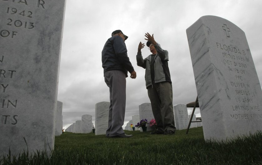 Navy veterans Raymond Moody, left, and Bob Browne, who both visit their wives graves most everyday, talk at the Miramar National Cemetery in San Diego on Thursday.