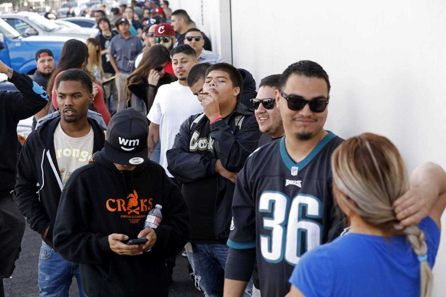 Anthony Ramirez, center, of Culver City, waits in line at the grand opening of Cookies Los Angeles, the city's first marijuana dispensary selling recreation use cannabis under Proposition 64.