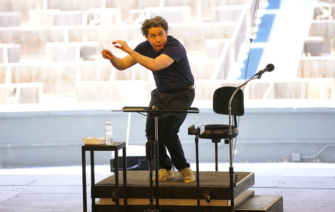 Dudamel conducts rehearsal with empty seats visible behind him
