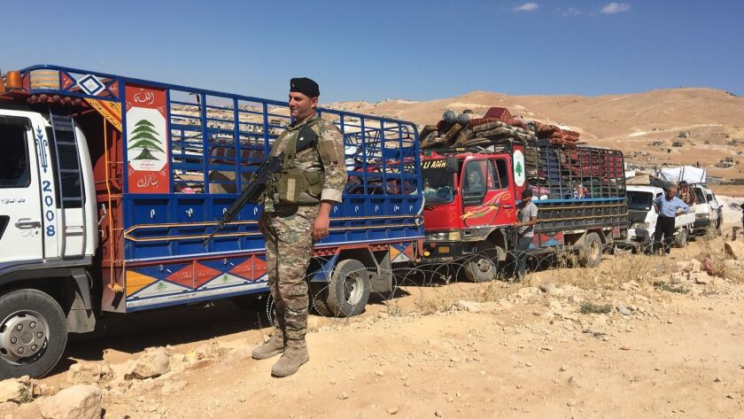 Members of the Lebanese armed forces watch over departing Syrian refugees at a checkpoint on the edg