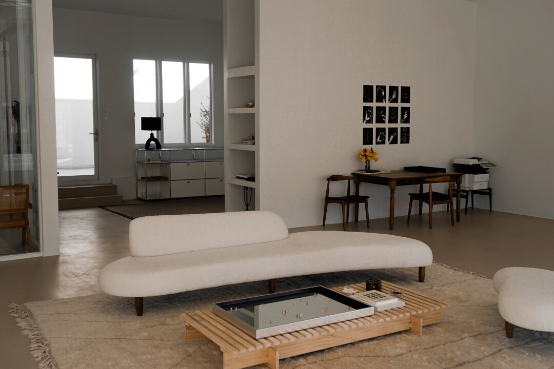 A white biomorphic couch and low wooden table inside Tase Gallery