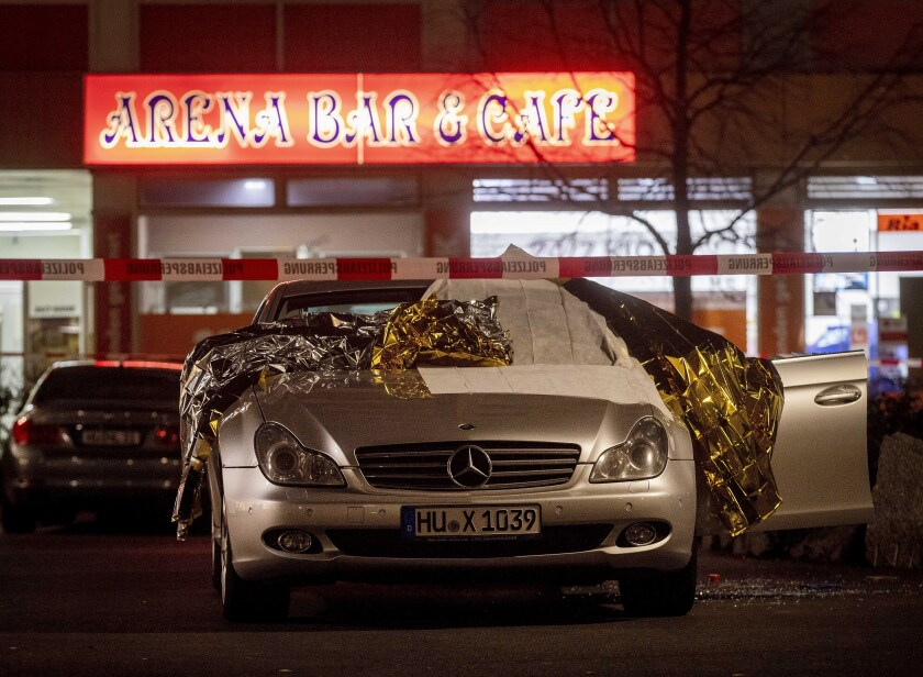Thermal blankets cover a car in Hanau, Germany, near the scene of a shooting Wednesday.