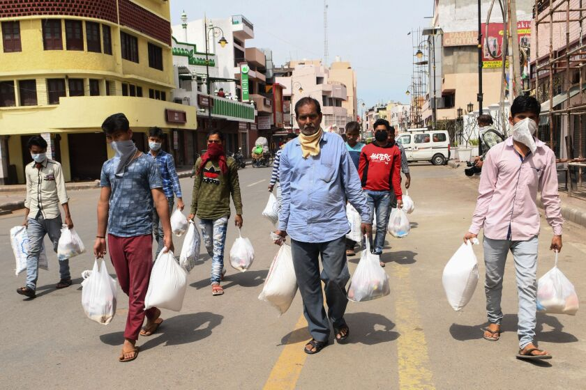 People carry grocery items distributed by volunteers in Amritsar, India.