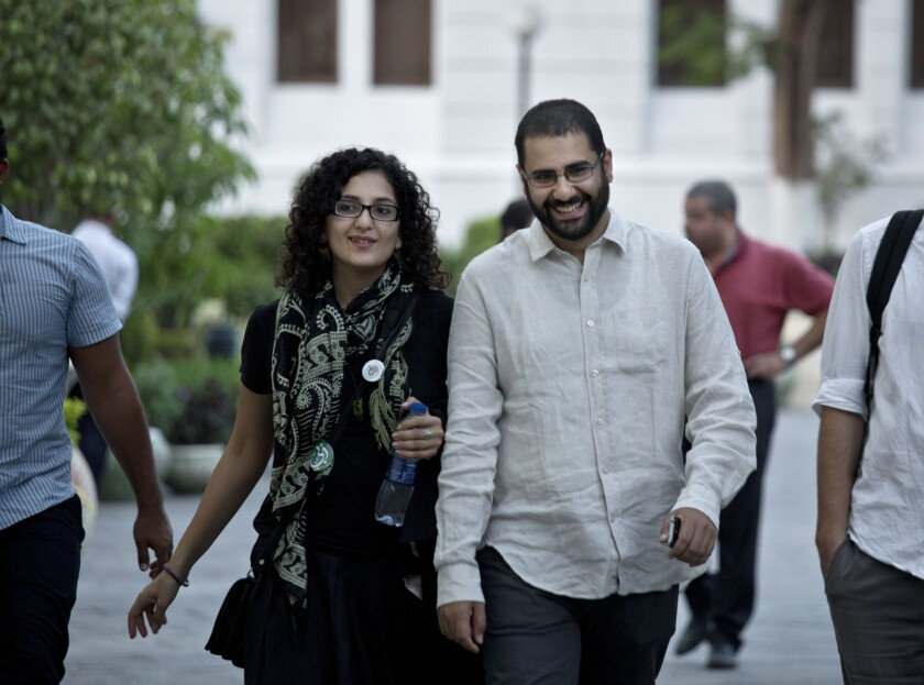 FILE - In this Sept. 22, 2014 file photo, Alaa Abdel-Fattah, a leading pro-democracy activist, walks with his sister Mona Seif prior to a conference at the American University in Cairo, near Tahrir Square, Egypt. The family of Abdel-Fattah, who was arrested amid the recent clampdown that followed anti-government protests, says he was beaten, threatened and stripped to his underwear while in custody. Seif, a prominent human rights activist tweeted on Thursday, Oct. 10, 2019, that her brother also told his lawyers that he was blindfolded and threatened that he would never set foot outside one of Cairo's most notorious prisons. (AP Photo/Nariman El-Mofty, File)