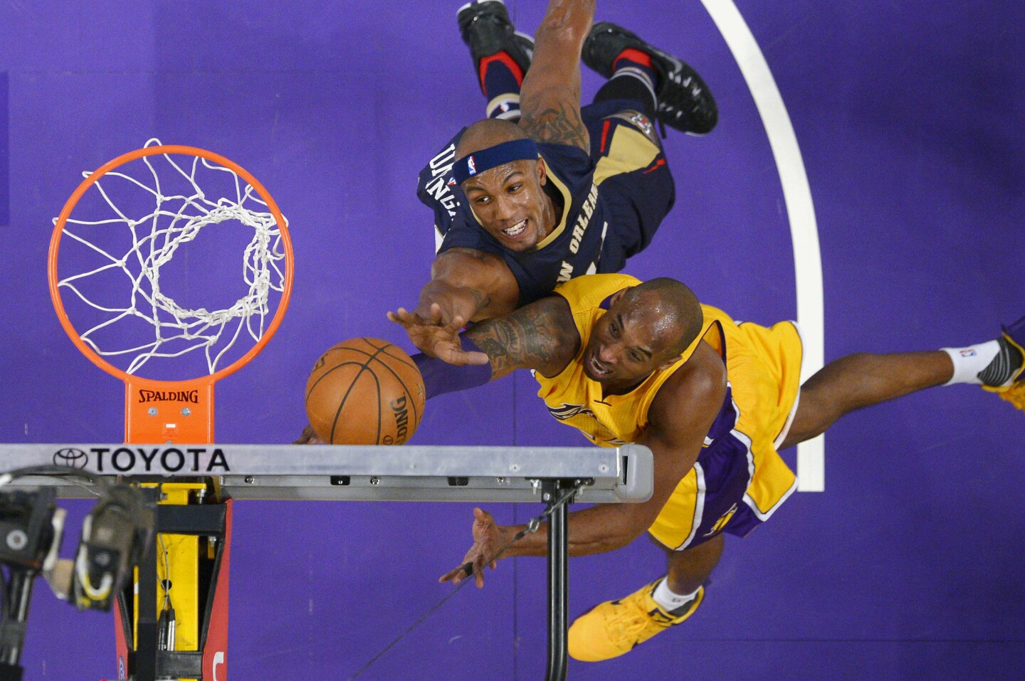 Lakers forward Kobe Bryant, right, shoots as Pelicans forward Dante Cunningham defends during the first half.