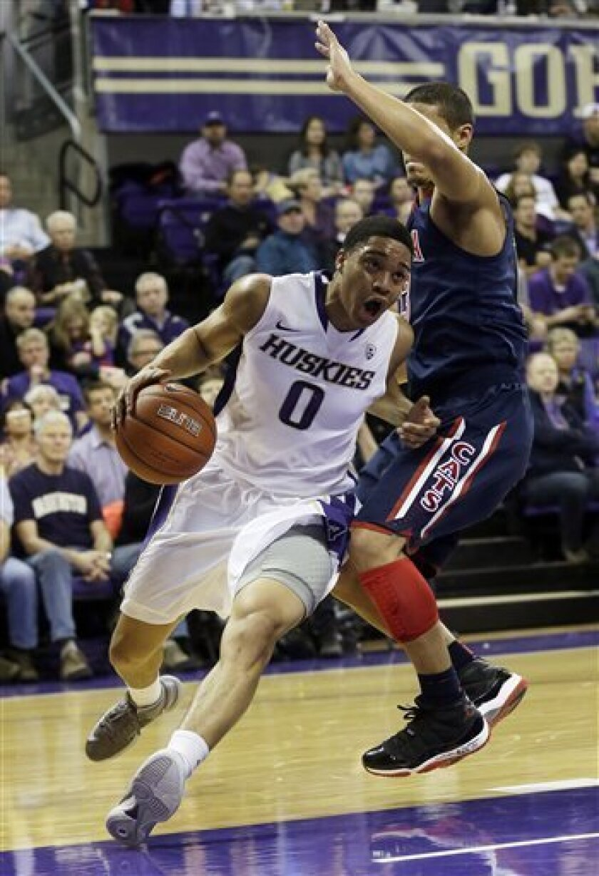 Washington's Abdul Gaddy (0) drives around Arizona's Nick Johnson, right, in the first half of an NCAA college basketball game, Thursday, Jan. 31, 2013, in Seattle. (AP Photo/Ted S. Warren)