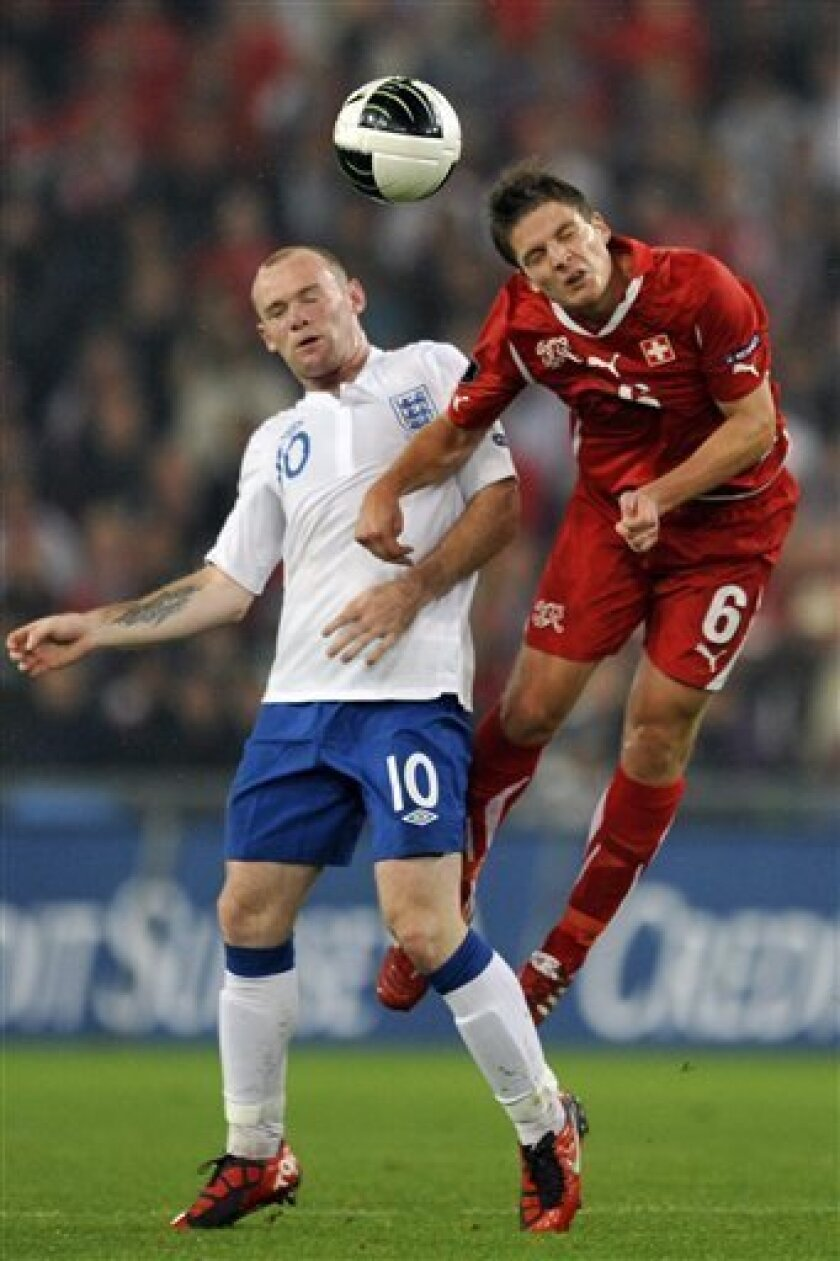 England's forward Wayne Rooney, left, challenges for the ball with Swiss midfielder Pirmin Schwegler, right, during the Euro 2012 group G qualification soccer match between Switzerland and England at the St. Jakob-Park Stadium in Basel, Switzerland, Tuesday, Sept. 7, 2010. (AP Photo/Keystone/Georgios Kefalas)