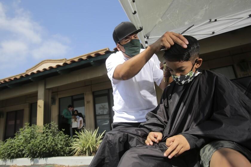 Keri Davis-Duffy, co-owner of the Gila Rut Aveda Salons in San Diego, supervises a haircut at Gila Rut salon.