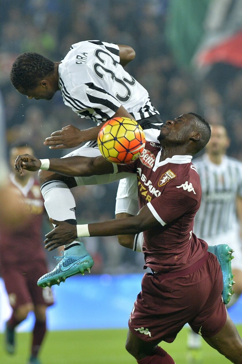 Juventus' Patrice Evra jumps for the ball with Torino Afriye Acquah during a Serie A soccer match between Juventus and Torino at the Juventus stadium, in Turin, Italy, Saturday, Oct. 31, 2015. (AP Photo/ Massimo Pinca)