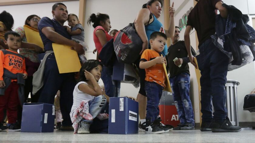 Immigrant families seeking asylum wait in line at the central bus station after they were processed