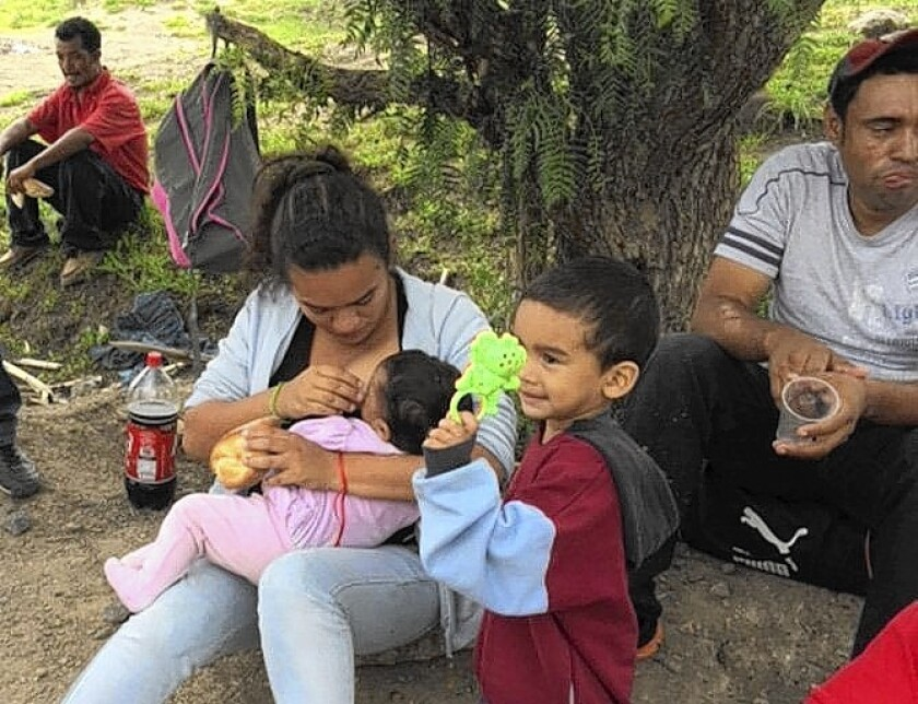 Claudia Sanchez of Honduras breast-feeds her daughter as they wait in Tequixquiac, Mexico, for the next freight train to carry them toward the U.S. border.
