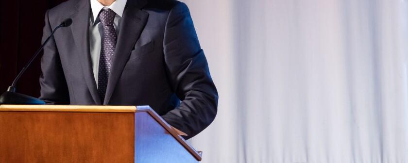 stock photo man in suit at podium