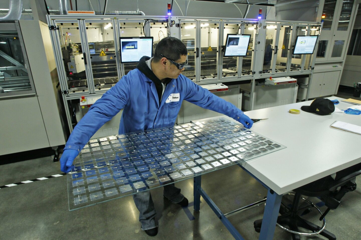 In this 2013 file photo, operator Peter Lancaster works on a solar module assembly line at Soitec in Rancho Bernardo.