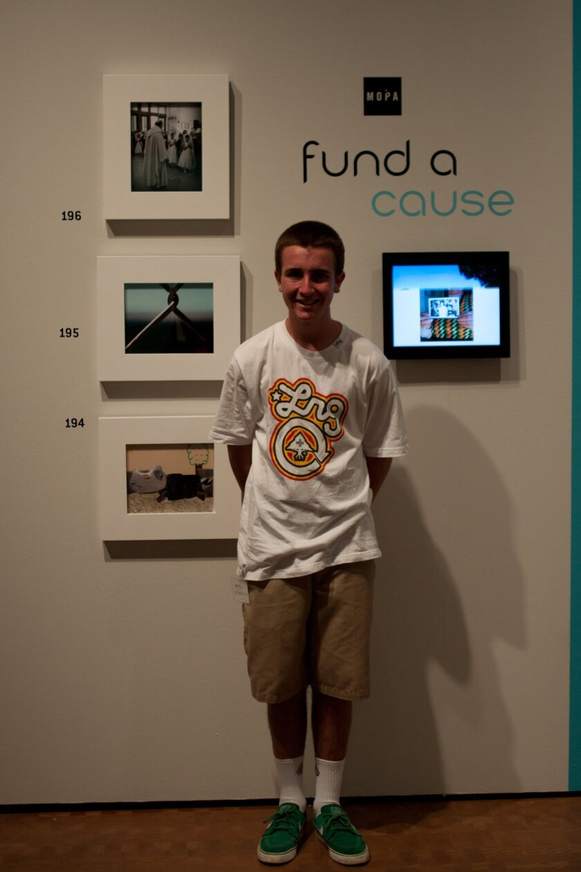 Michael Mitchell poses at the Museum of Photographic Arts in Balboa Park with his work, center right. Courtesy