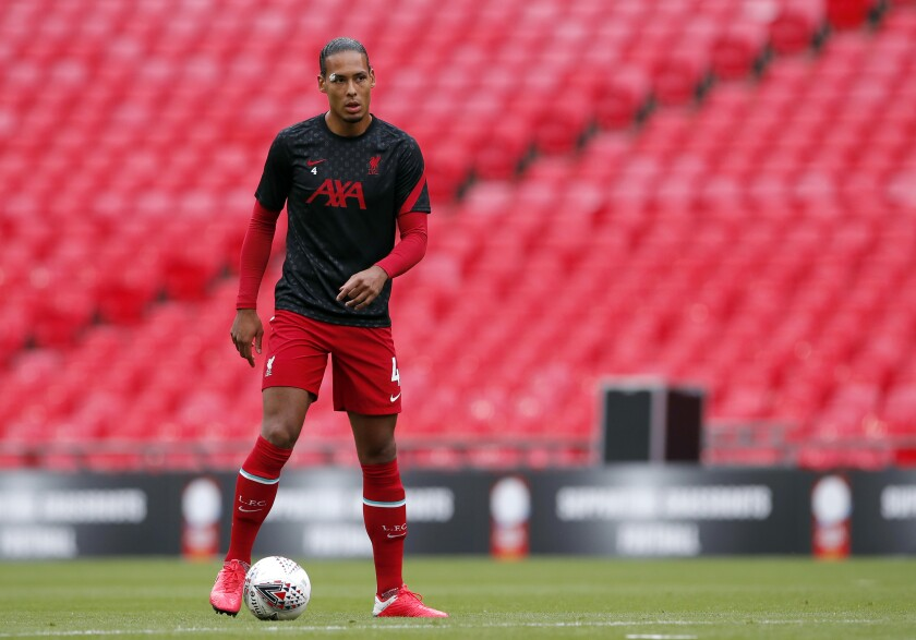 """Liverpool's Virgil van Dijk warms up before their English FA Community Shield soccer match against Arsenal at Wembley stadium in London, Saturday, Aug. 29, 2020. Liverpool center-back Virgil van Dijk says he is """"ready to crack on"""" with more minutes in the club's next pre-season match as he returns from knee surgery. It's still unclear though if he'll be ready for the start of the new season. Norwich visits Anfield for the Aug. 14 season opener but Van Dijk says he's just focused on increasing his workload Thursday, Aug. 5 2021 in a friendly against Bologna at the Premier League team's training camp in Evian, France. (Andrew Couldridge/Pool via AP, file)"""