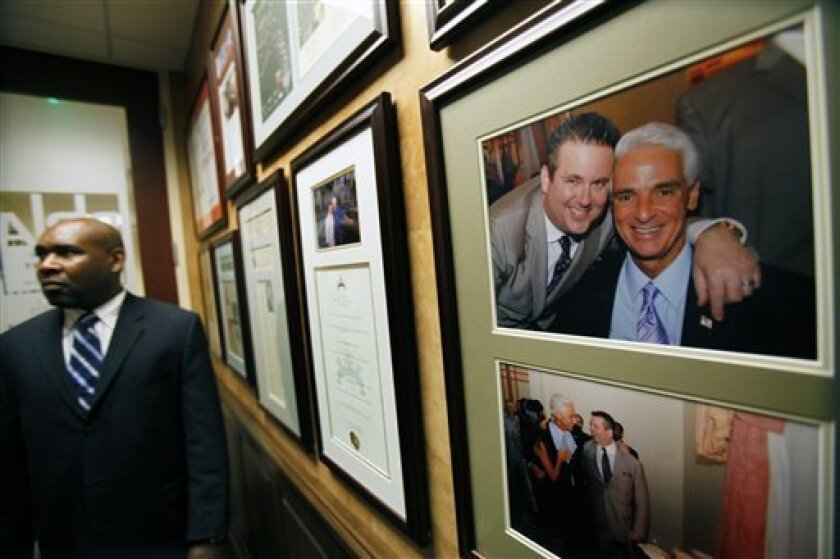 FILE - In this Nov. 5, 2009 file photo of attorney Scott Rothstein, left, and Gov. Charlie Crist, FL-R, hangs in the law offices of Rothstein Rosenfeldt Adler, in Fort Lauderdale, Fla. Rothstein, who lived lavishly and courted both politicians and celebrities was arrested Tuesday, Dec. 1, 2009 on federal charges that he operated a $1 billion investment fraud scheme using faked legal settlements. (AP Photo/Wilfredo Lee, File)