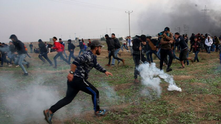 Palestinian protesters run for cover from teargas fired by Israeli soldiers during clashes on the Is