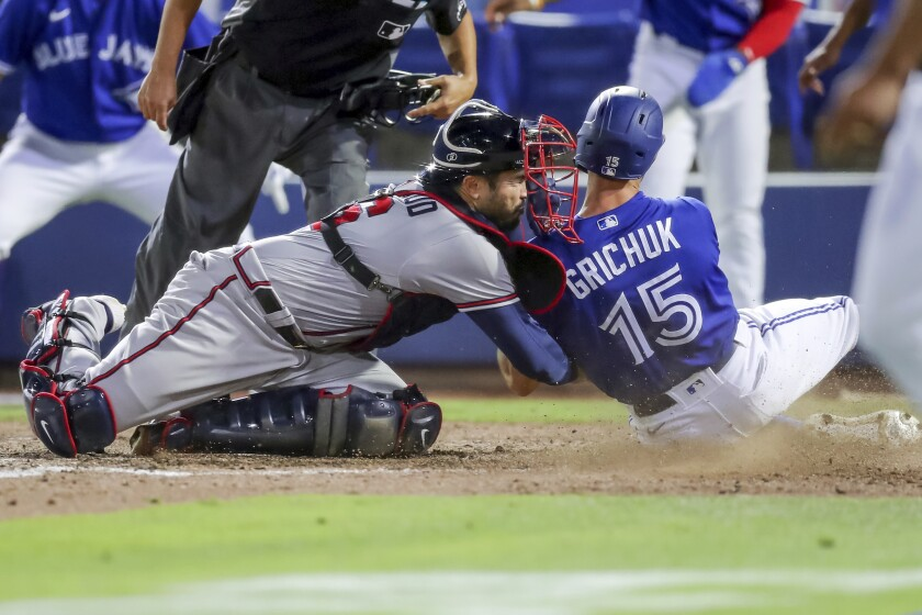 Atlanta Braves catcher Travis d'Arnaud tags out Toronto Blue Jays' Randal Grichuk during the sixth inning of a baseball game Saturday, May 1, 2021, in Dunedin, Fla. (AP Photo/Mike Carlson)