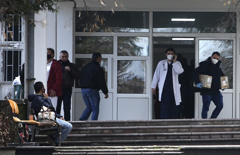 In this picture taken on Tuesday, Dec. 29, 2020, people and health workers are pictured in front of the entrance of the University Clinic complex in Skopje, North Macedonia. When thousands of people across the European Union simultaneously began rolling up their sleeves last month to get a coronavirus vaccination shot, one corner of the continent was left behind, feeling isolated and abandoned: the Balkans. (AP Photo/Boris Grdanoski)